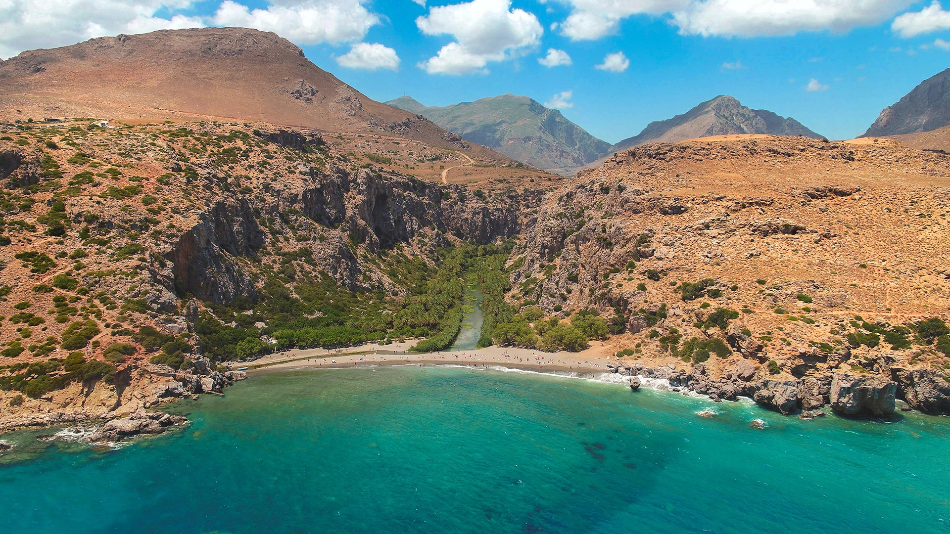 Preveli beach, with its palm grove, saltwater lagoon and dramatic Cretan gorge as scenery