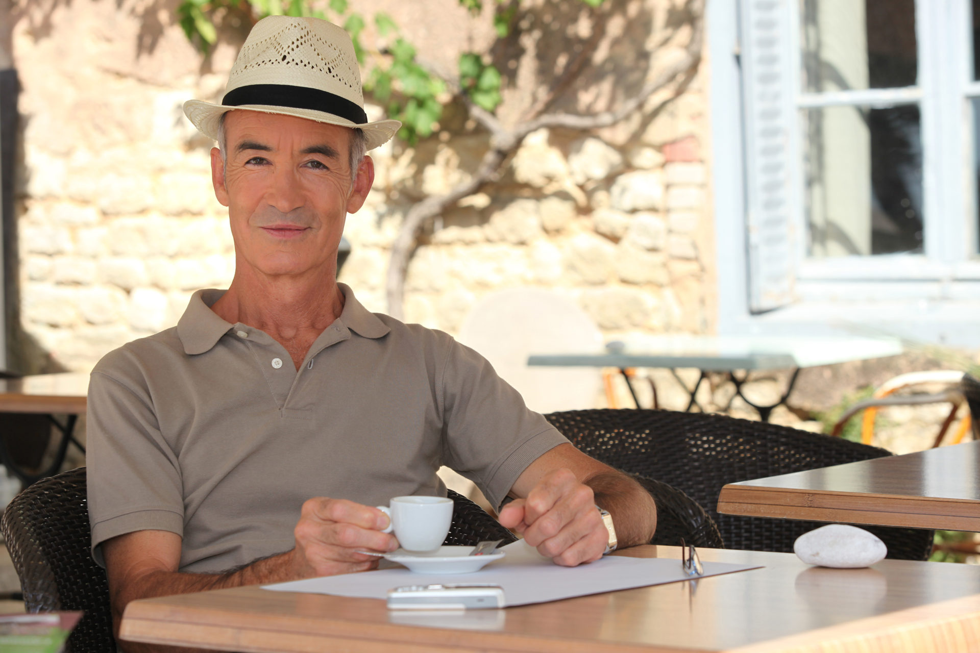 Elderly man enjoying a cup of coffee in a cafe