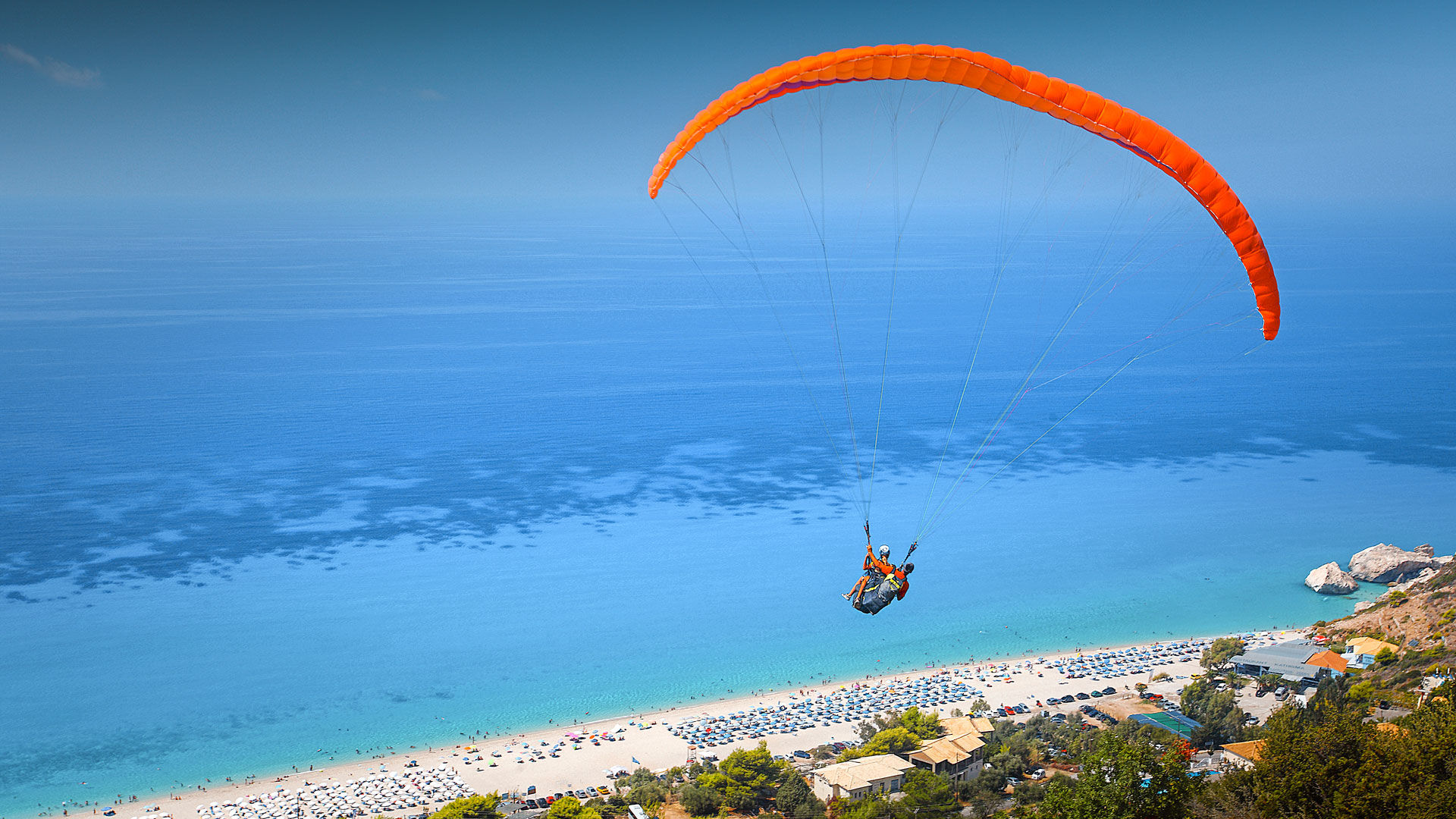 The sight of the paragliders, who launch from the green mountain backdrop and arc overhead before settling on the beach
