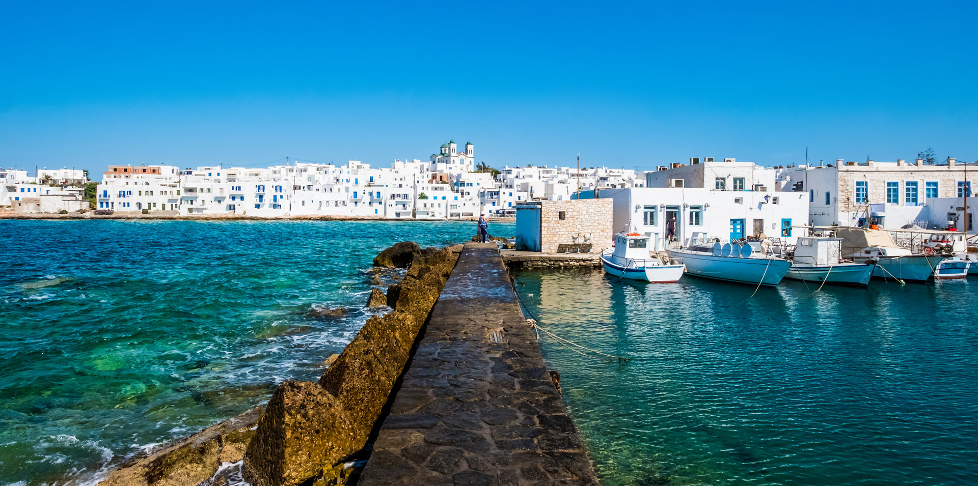 View of the traditional white houses on the promenade of Naoussa Paros, from the harbor on a sunny day