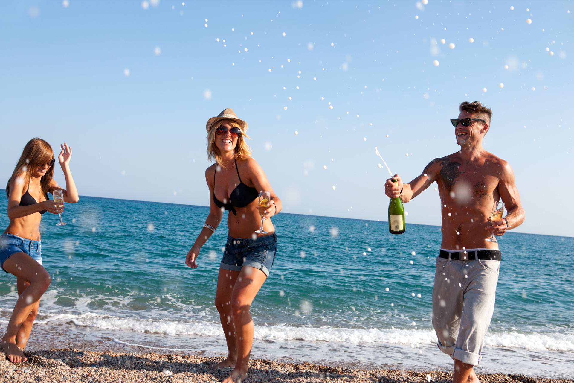 Group of friends dancing under champagne bubbles on beach