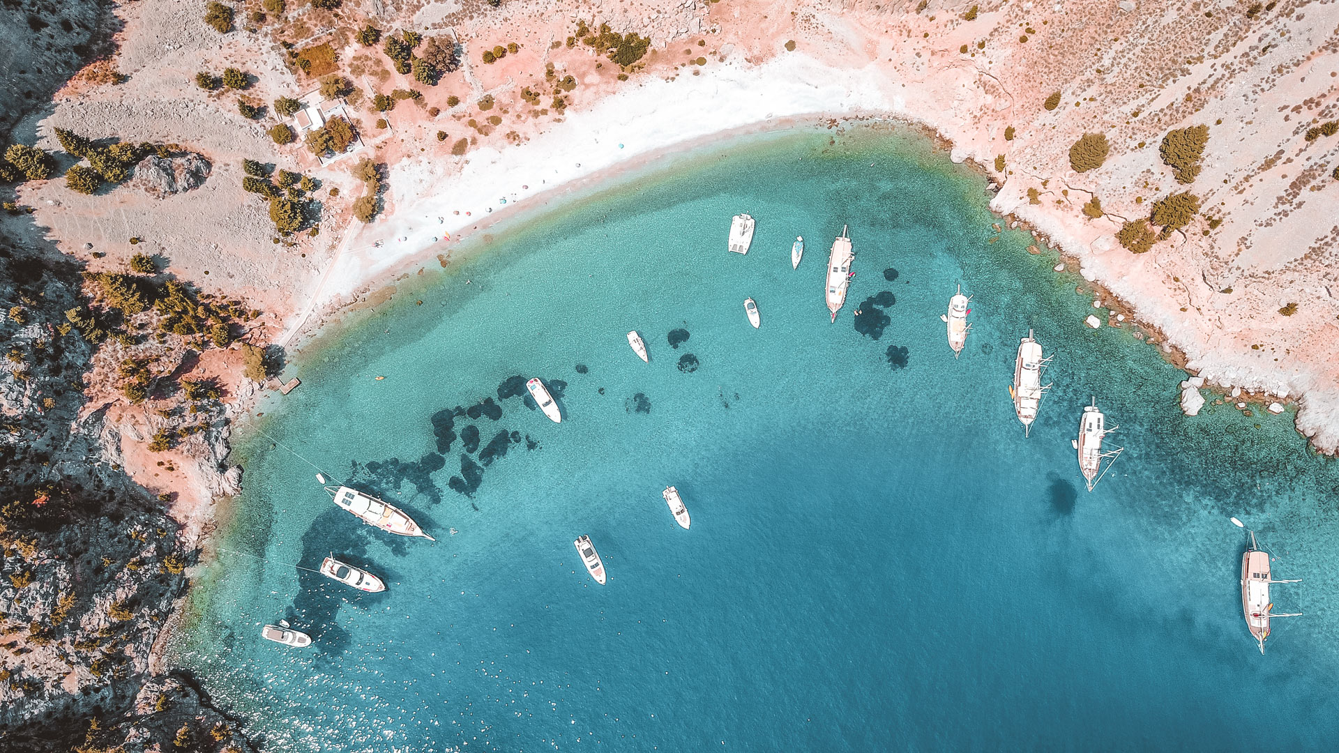 The famous tropical rocky beach of Agios Georgios with yachts docked, Symi island