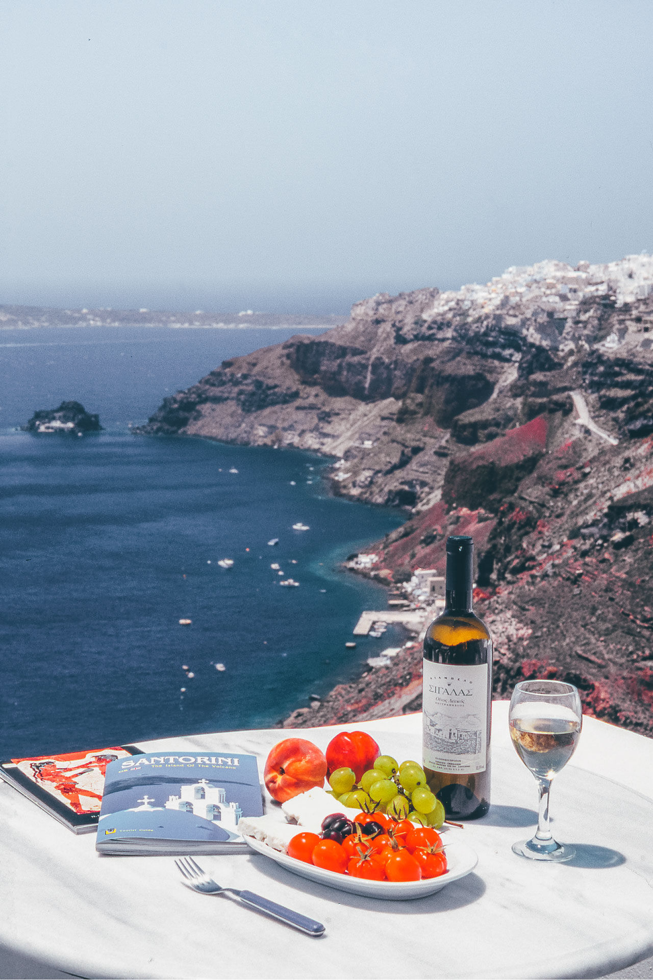 The delicious white wine of Santorini accompanied with cherry tomato-the most famous product of the island