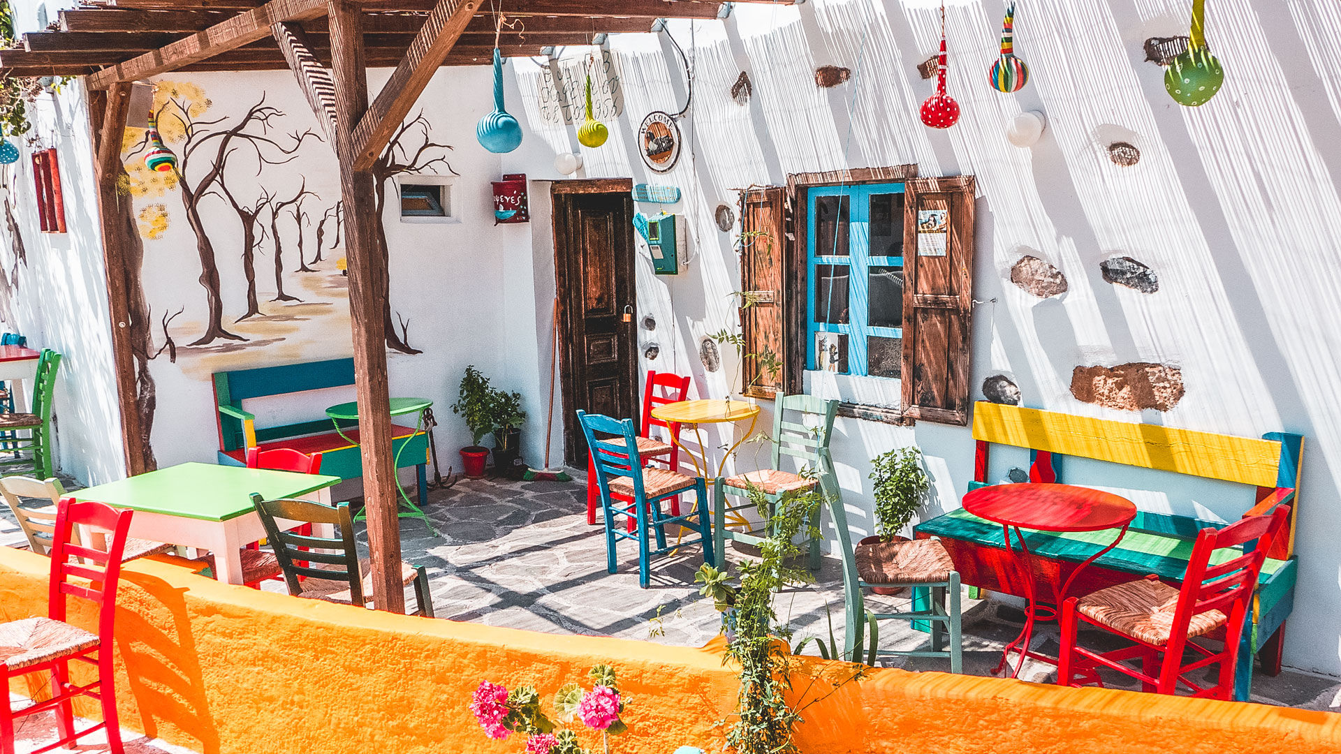 Whitewashed houses, blue windows, flowery courtyards and colorful cafes in Maltezana village, Astypalea