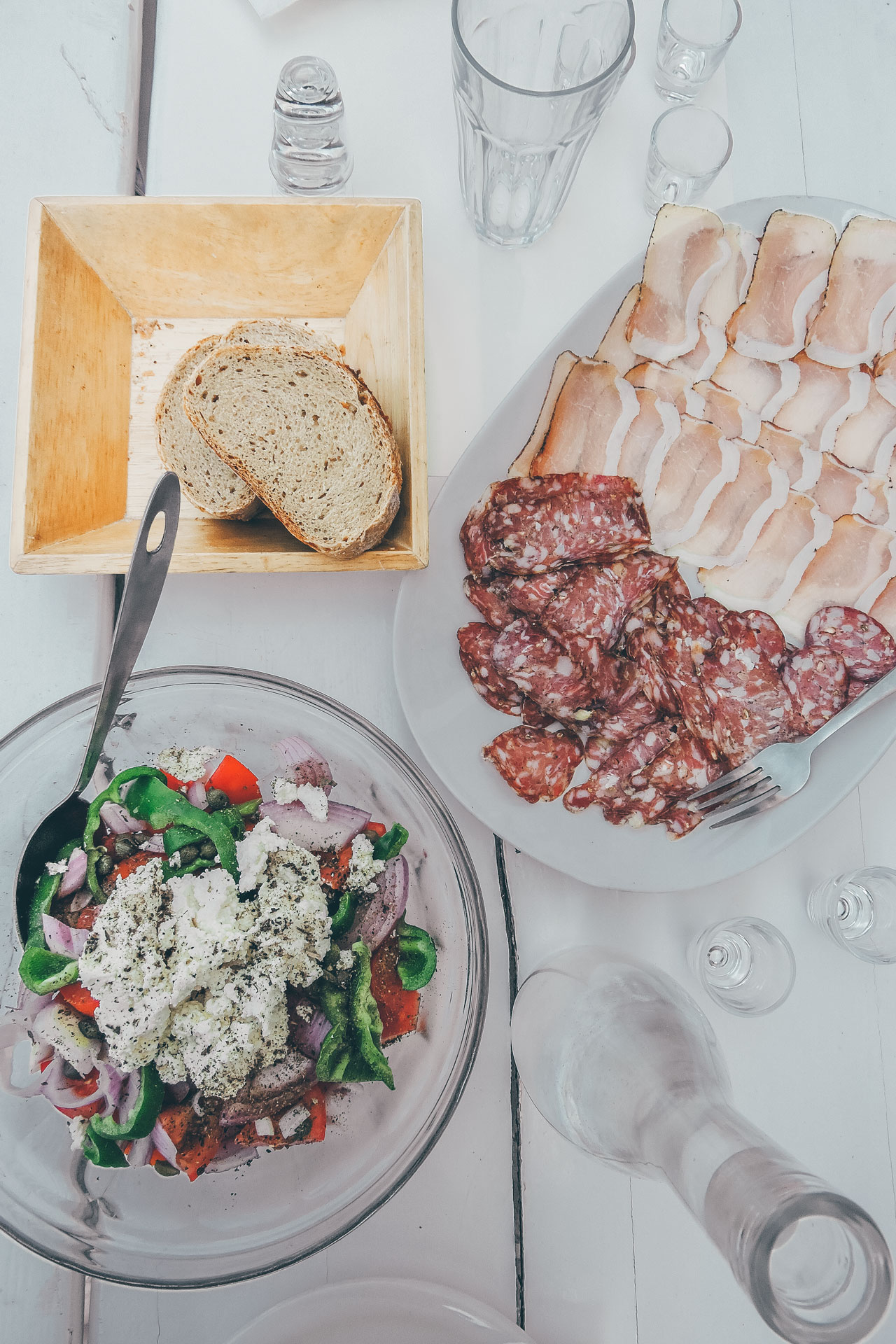 A delicious country sausage or syglino (small pieces of cured pork), accompanied with Greek salad and raki