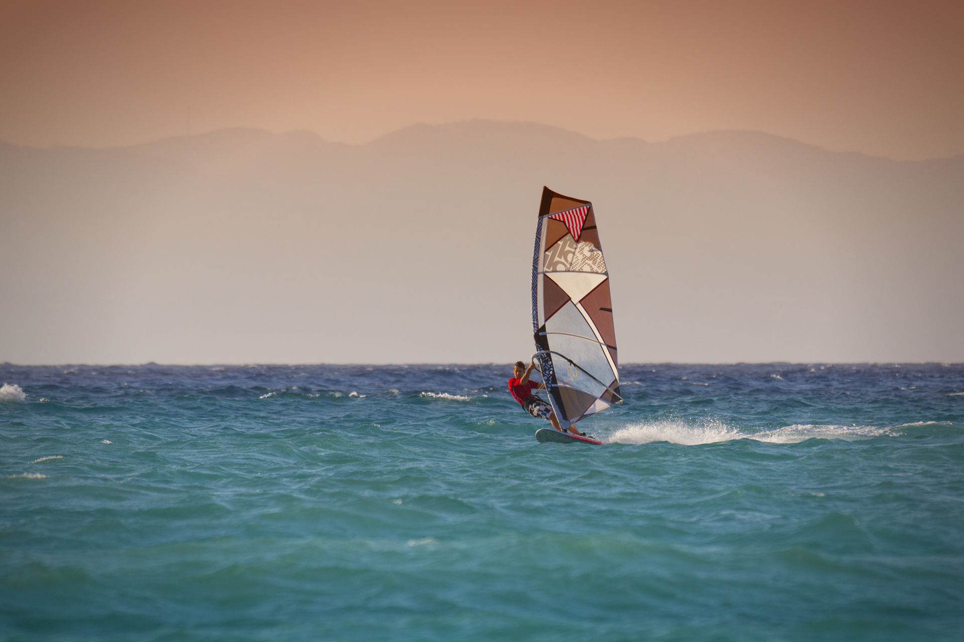 Windsurfing in Rhodes Greece_Man surfing on blue with oceanwith red sky