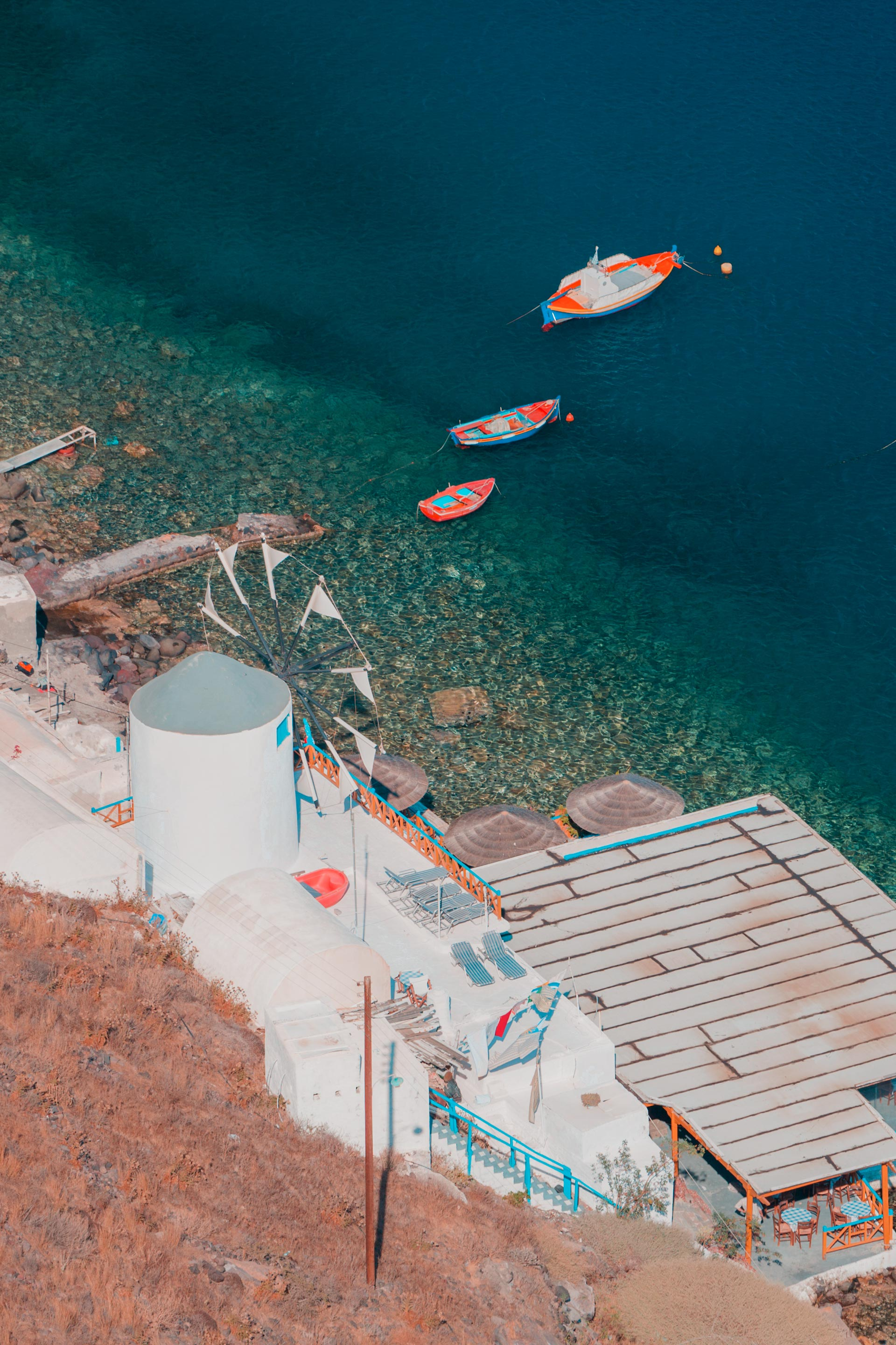 Boats and a windmill in the harbor Ormos Korfou in Thirassia seen from above
