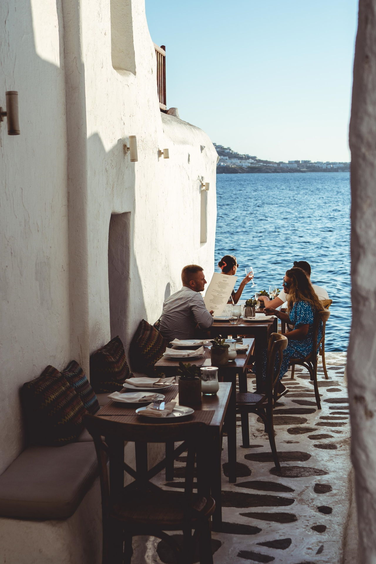 Dining in Cycladic alleyway by the sea in Mykonos.