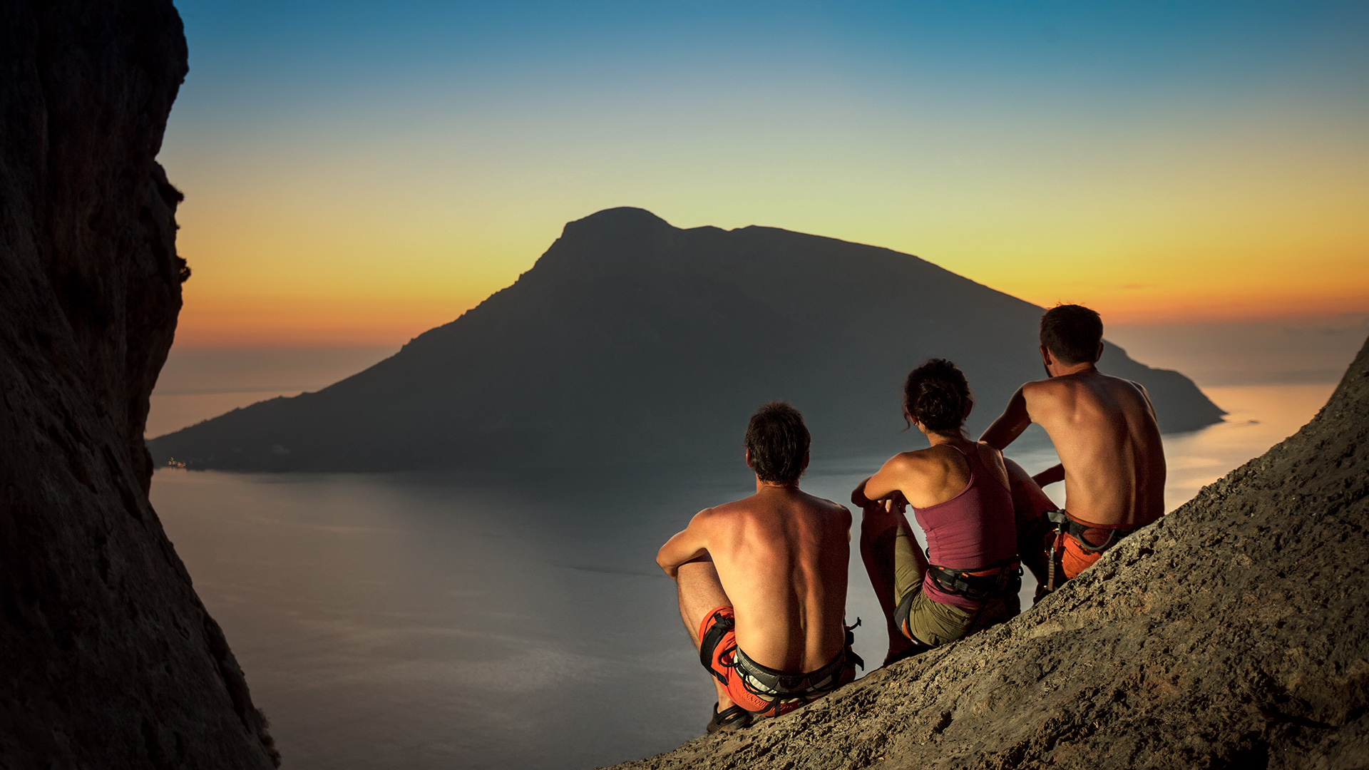 Rock climbers admiring the sunset view of Telendos islet opposite from Kalymnos island