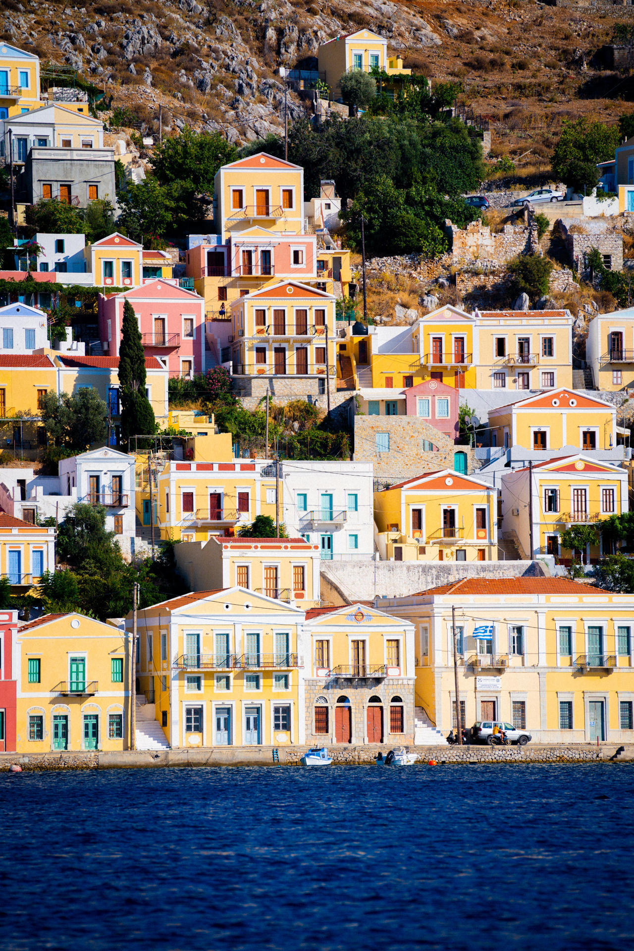 Appreciate the colours and grandeur of the mansion houses rising up the hill in Gialos
