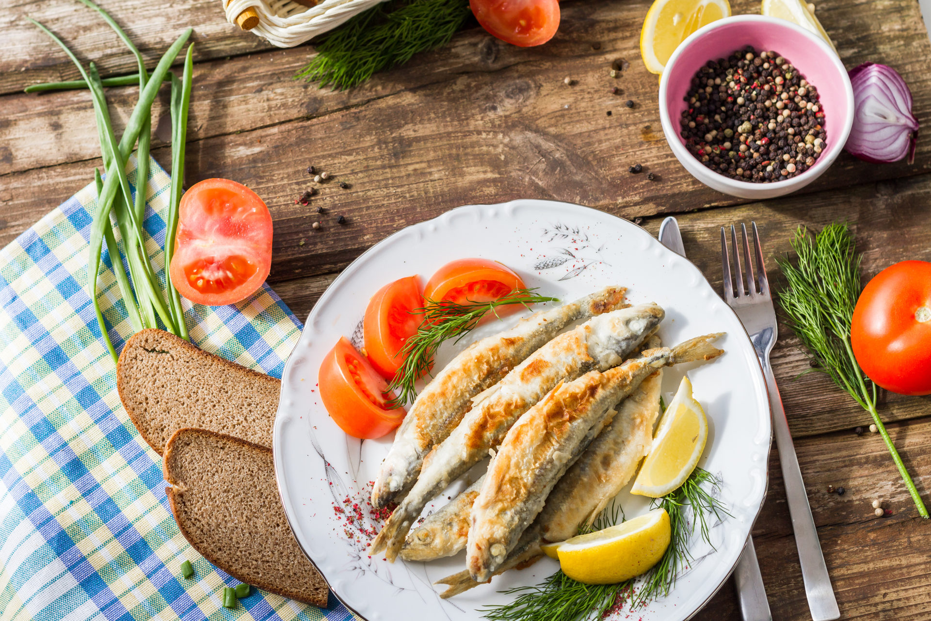 Fried fish smelt on a plate, served with lemon, tomatoes, onions and herbs