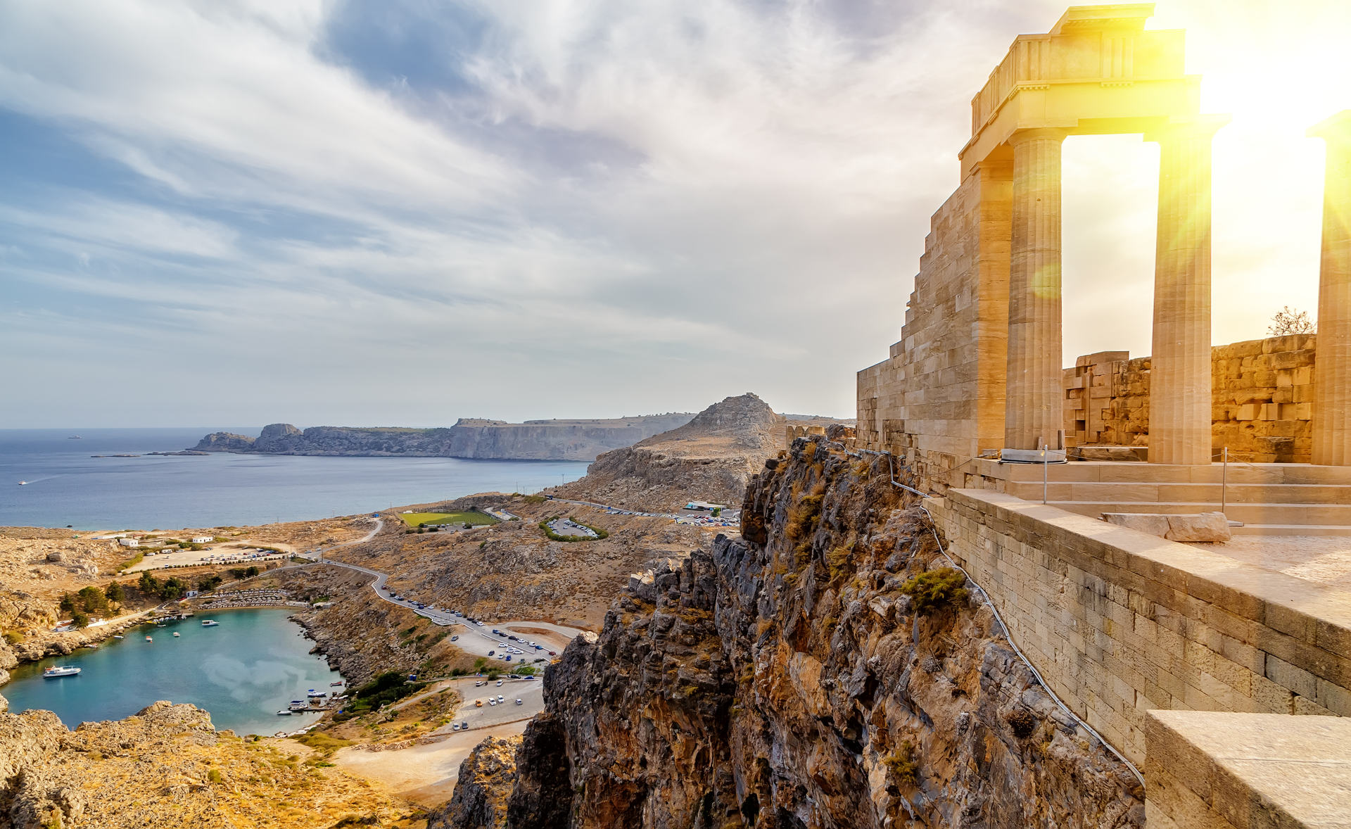 Acropolis of Lindos. Doric columns of the ancient Temple of Athena Lindia setting sun above the columns T