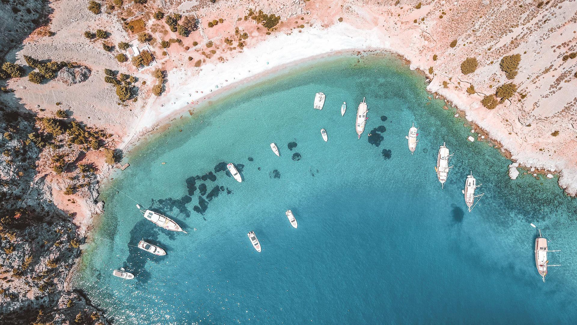 The famous tropical rocky beach of Agios Georgios with yachts docked, Symi island, Dodecanese