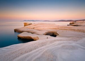 Coastal scenery with pale volcanic rocks near Sarakiniko beach in Milos island, Greece. Kimolos island can be seen in the distance.