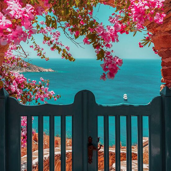 Picturesque bougainvillea and a door leading to a beautiful beach, on Ios island