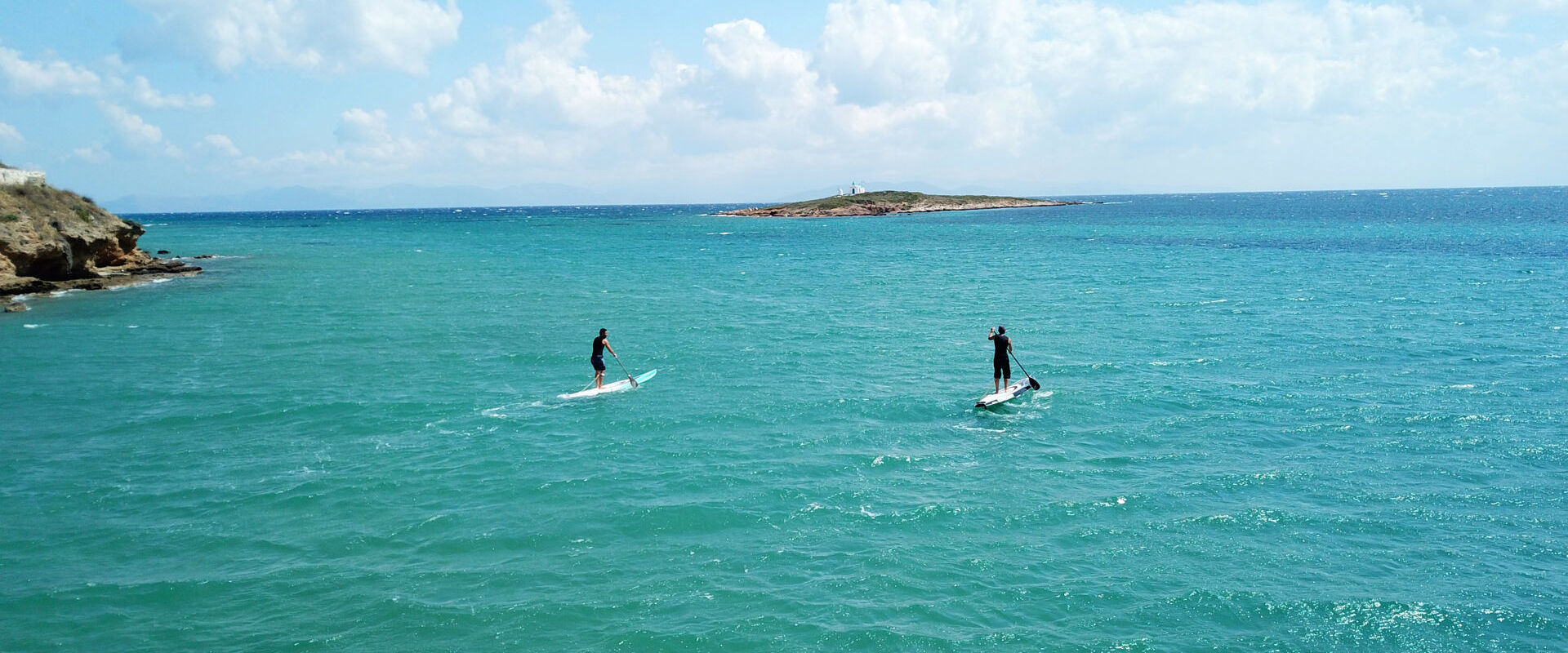 Aerial photo of competition sport paddle surfing or sup between 2 men in tropical waters of Vouliagmeni beach, Athens riviera, Attica, Greece