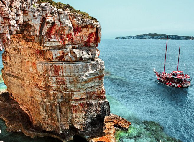 Boat passing next to Trypitos (also known as Kamara), a natural rocky arch at Paxos island