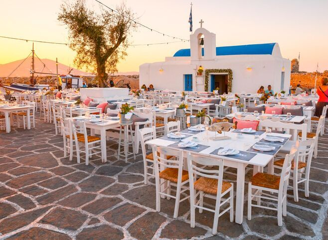 Tables of a restaurant in front of a church in the harbour of Naousa village, Paros island