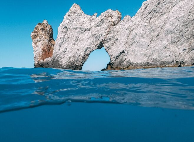 There is a portal-like rock (Tripia Petra) through which you can swim or kayak into another world